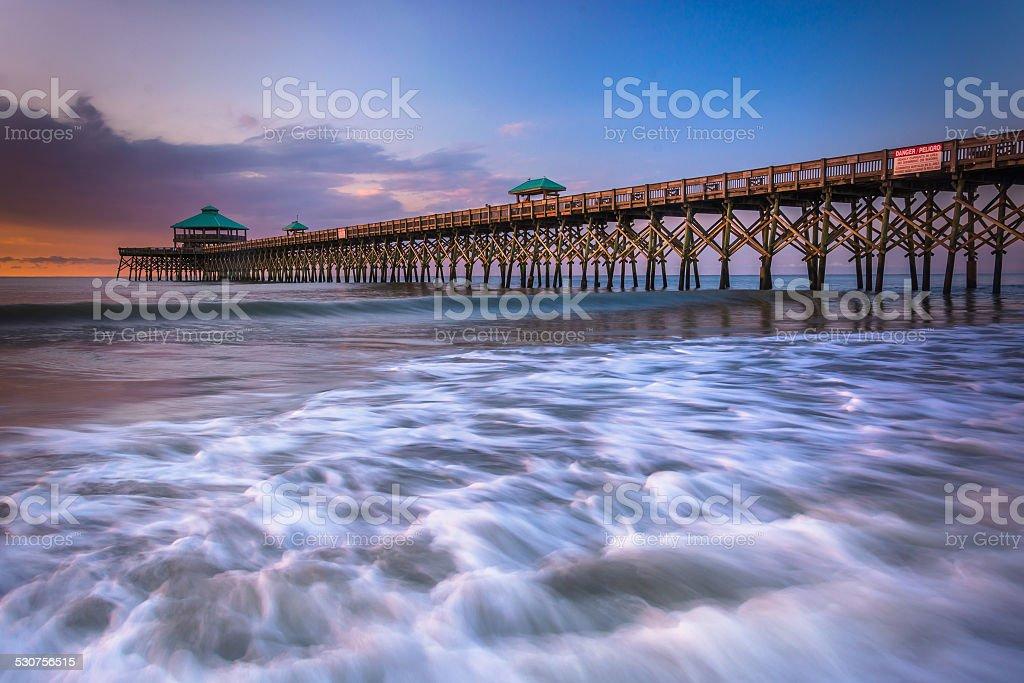 The fishing pier at sunrise, in Folly Beach, South Carolina. stock photo