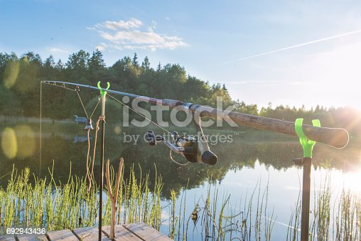 1094918172istockphoto The fishing-rod standing on a support thrown in water for fishing. 692943436