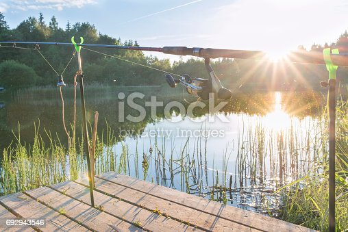 1094918172istockphoto The fishing-rod standing on a support thrown in water for fishing. 692943546