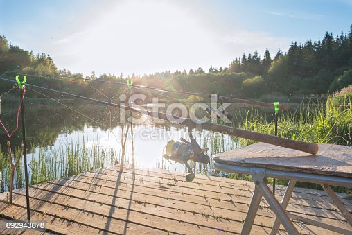 1094918172istockphoto The fishing-rod standing on a support thrown in water for fishing. 692943678