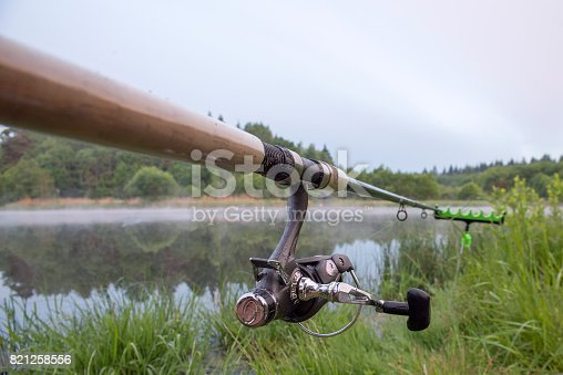 1094918172istockphoto The fishing-rod standing on a support thrown in water for fishing. 821258556