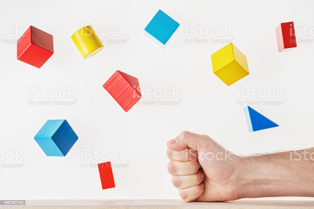 The fist strikes the table and the multicolored wooden geometric shapes fly around. Concept of creative, logical thinking. Floating shapes. stock photo