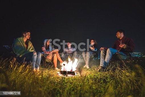 The five people rest near the bonfire. evening night time