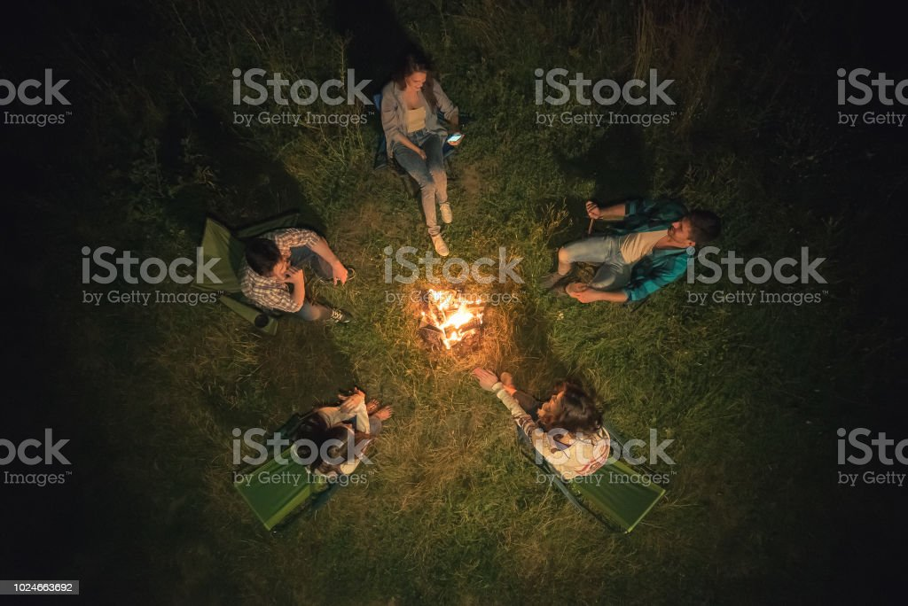 The five people sit near the bonfire. night time, view from above