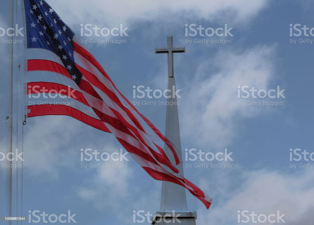 The flag and the cross The American Flag flies over a steeple with the Christian Cross American Flag Stock Photo