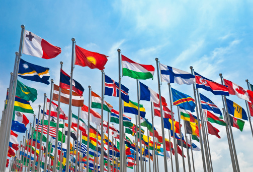 waving in the wind flags of different countries with blue sky on background
