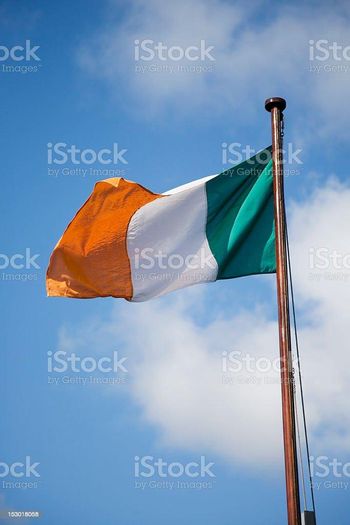 The flag of Ireland hoisted against blue sky stock photo
