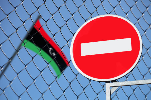 the flag of Libya behind the fence with the sign is forbidden stock photo