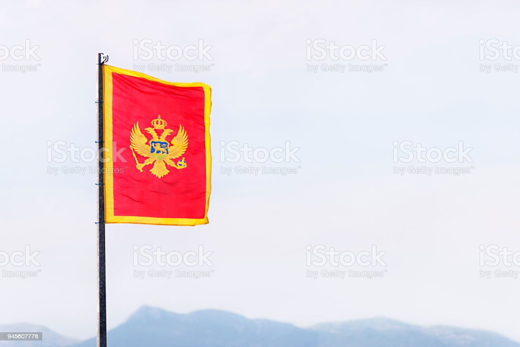 The flag of Montenegro (red, with the two-headed eagle coat of arms in the middle, and golden borders) officially adopted on 13 July 2004 in statehood day. stock photo