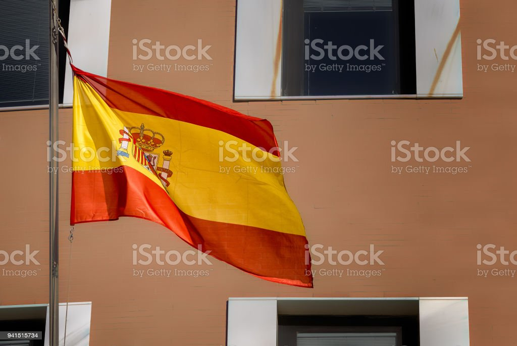 The flag of Spain flies on a pole in front of building. stock photo