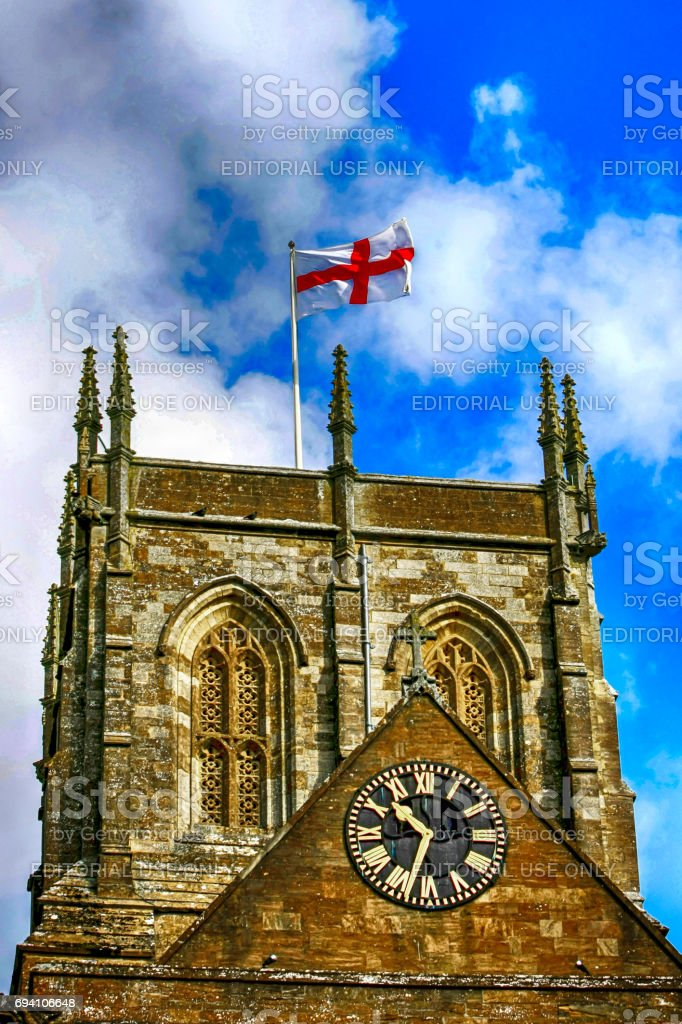 The flag of St George flies on April 23rd from the church tower in Dorset UK stock photo