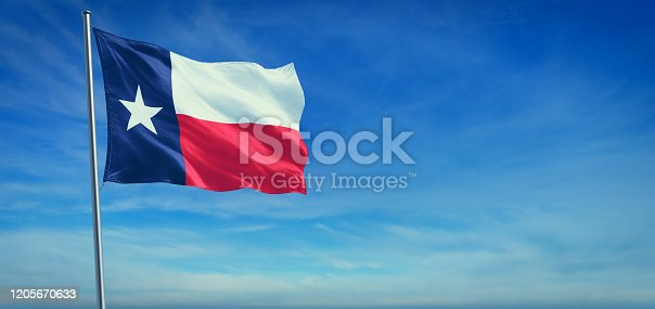 The flag of Texas state USA blowing in the wind in front of a clear blue sky