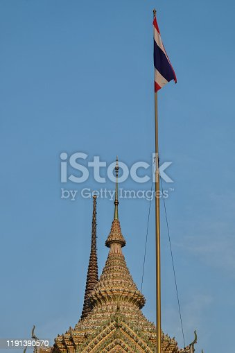 The flag of Thailand flaps on the flagpole above the temple spire.