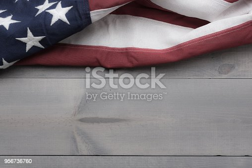 istock The flag of the United Sates on a grey plank background with copy space 956736760