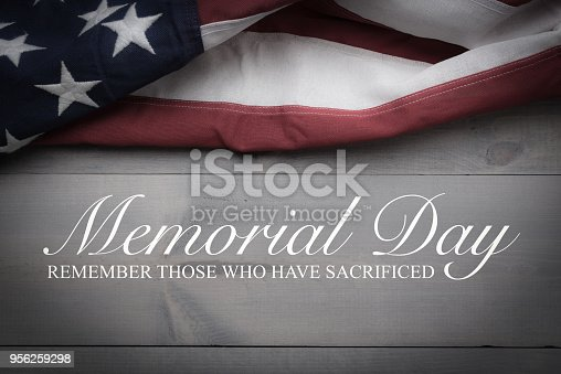 istock The flag of the United Sates on a grey plank background with memorial day 956259298