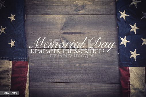 istock The flag of the United Sates on a grey plank background with memorial day 956737380