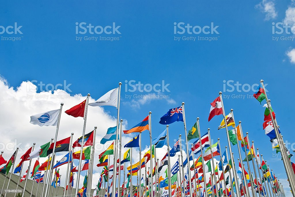 The flags of many countries on poles waving together stock photo