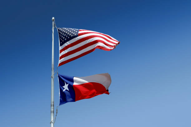 The flags of the United States and of the State of Texas on one flag-pole. stock photo