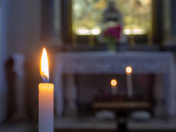 The flame of a candle with the church altar in the background - foto stock