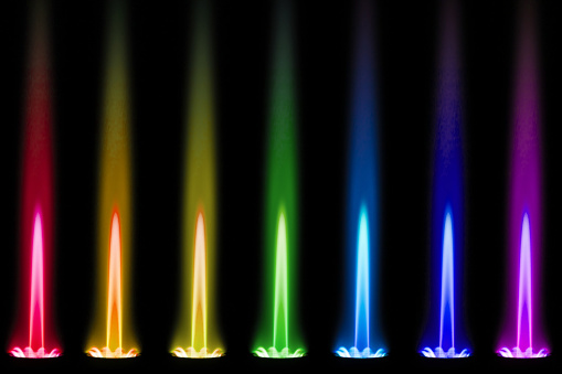 The flame of a gas burner shines like a rainbow in the dark