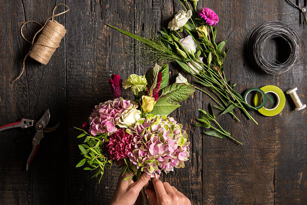 the florist desktop with working tools and ribbons - bouquet stock photos and pictures