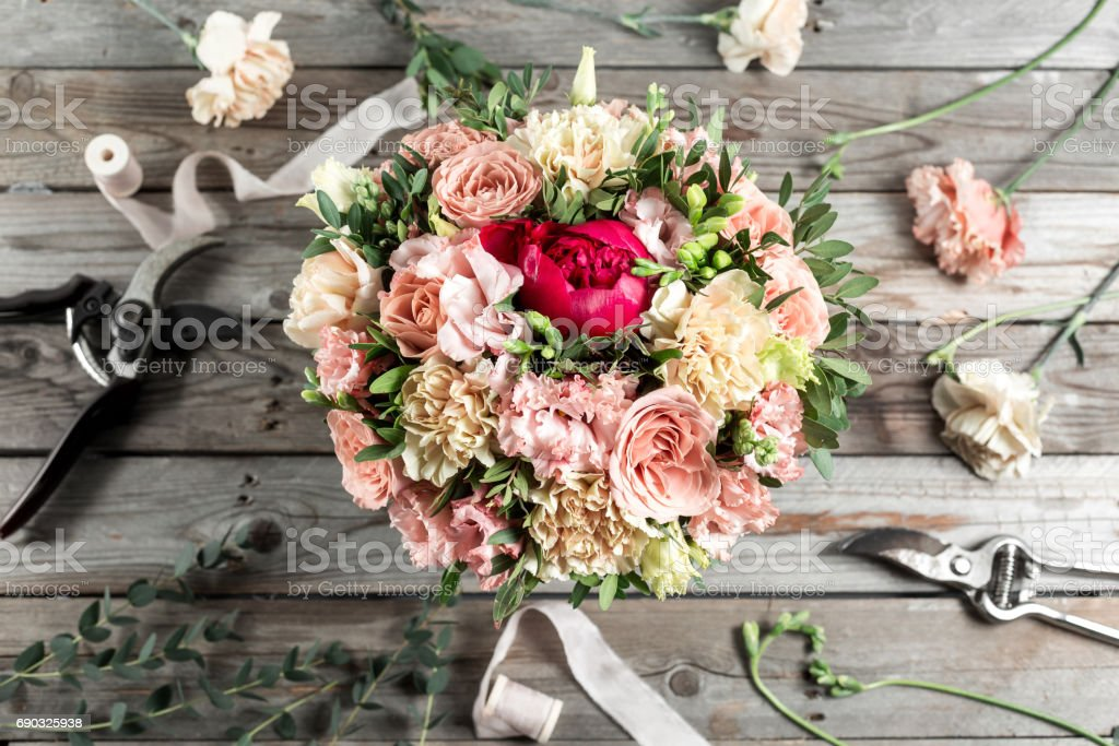 The florist desktop with working tools on gray old wooden background stock photo