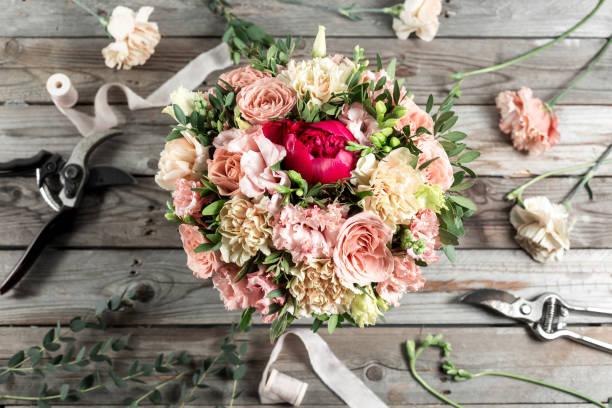 der florist-desktop mit arbeitswerkzeugen auf grauen alten hölzernen hintergrund - blumenarrangement stock-fotos und bilder