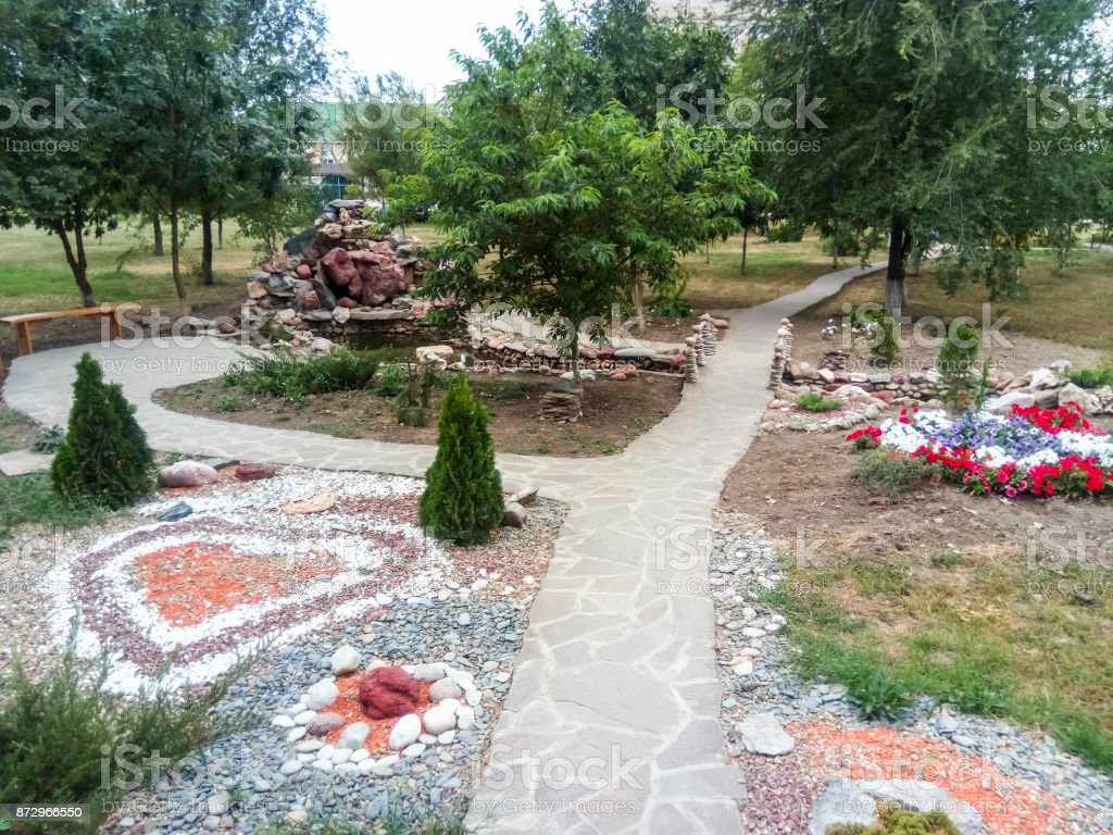 The flower bed is decorated with figures of stones of different colors. Hospital patio. stock photo