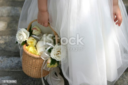 A flower girl holds a basket of flowers before a wedding ceremony