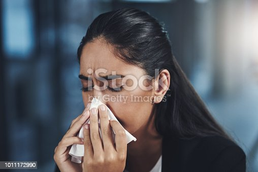 Shot of a young businesswoman blowing her nose in an office