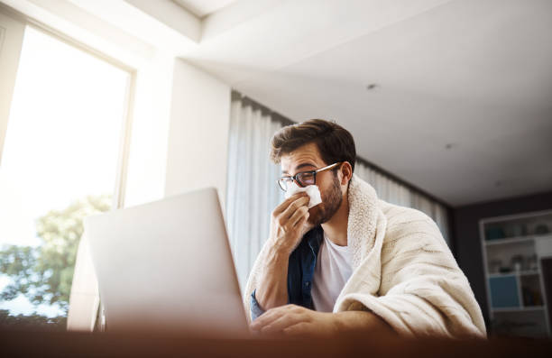 The flu has got him working from home today Shot of a sickly young businessman blowing his nose with a tissue while working from home allergy stock pictures, royalty-free photos & images