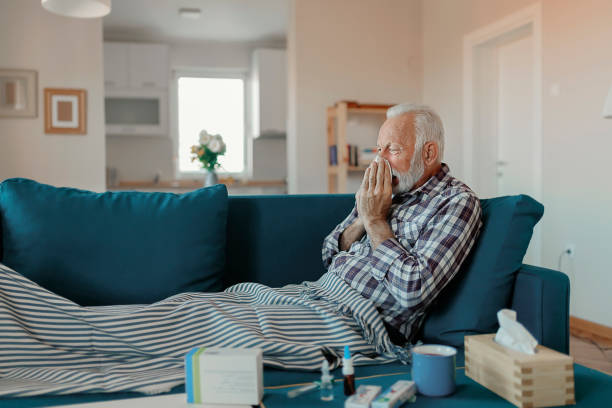 The Flu Cold exhausted senior man with flu wrapped in a warm blanket blowing his nose with a tissue in the livingroom flu stock pictures, royalty-free photos & images