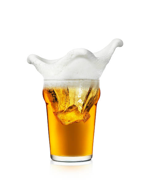 the foam on a glass of beer splashing the edges of the cup - beer foam stock photos and pictures