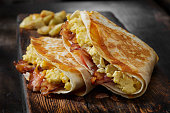 istock The Folded Breakfast Tortilla with Scrambled Eggs, Bacon, Tomato and Cheese 1299661454