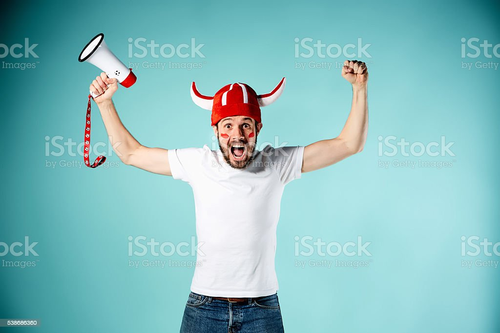 The football fan with mouthpiece over blue stock photo