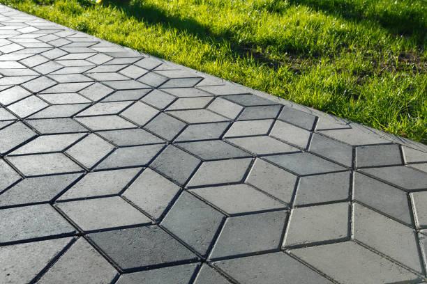 der fußweg im park ist mit diamantförmigen betonfliesen gepflastert. - auffahrt stock-fotos und bilder