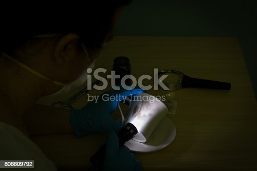 istock The forensic expert finds a fingerprint on the cups with brush and black powder in the dark 806609792