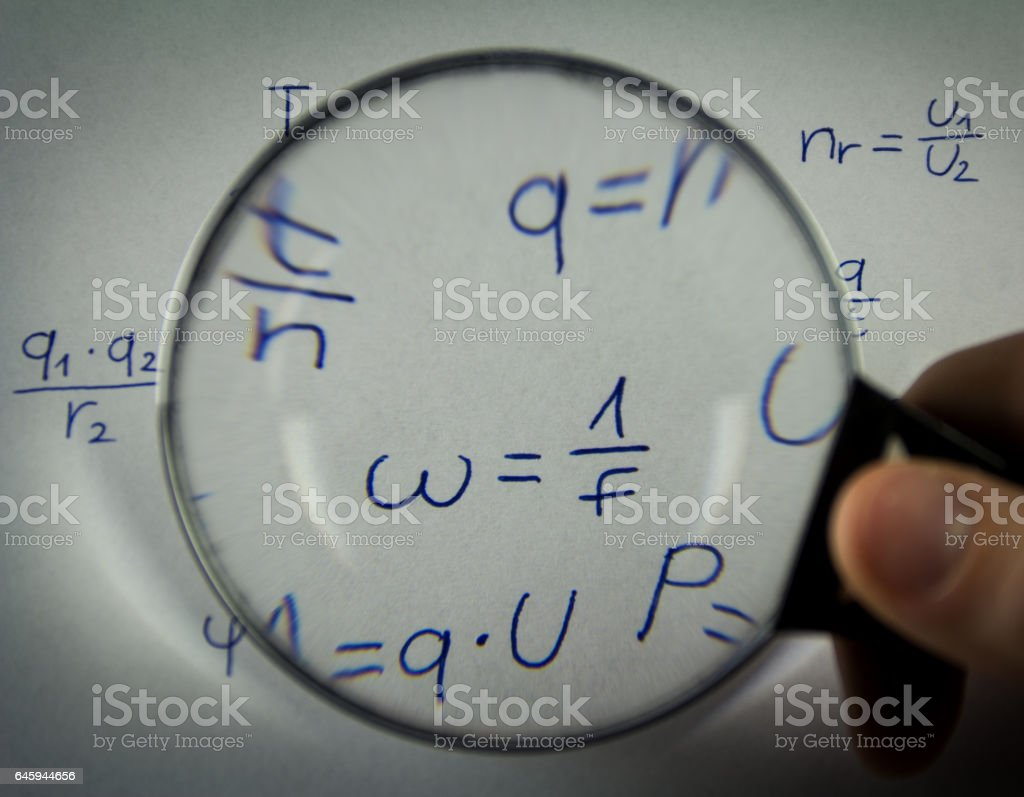 The formulas in physics watching through a magnifying glass stock photo