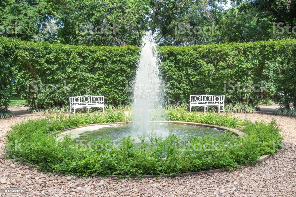 The fountain in the green garden is so hilarious. stock photo