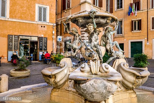 Rome, Italy, February 20 -- A view of Piazza Mattei and the delightful Fountain of the Turtles, a Renaissance fountain with bronze figures of young boys, turtles and dolphins, attributed to the architect Giacomo della Porta and created in 1581 in the heart of the Jewish Ghetto of Rome. The iconic Jewish quarter of Rome, the oldest Jewish ghetto in Europe, is constantly visited by tourists due to the presence of hidden alleys and small squares, where it is easy to find restaurants of Italian and Jewish cuisine and notable Roman archaeological remains. Image in High Definition format.