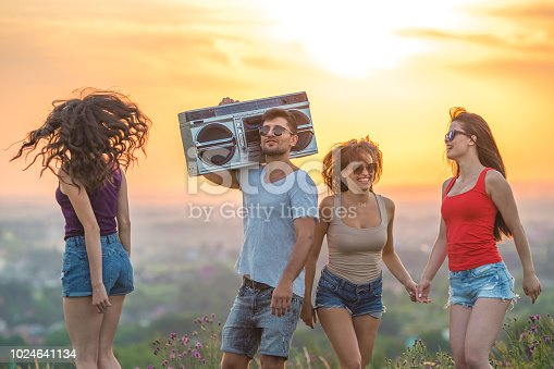 The four people dancing with a boom box on the sunset background