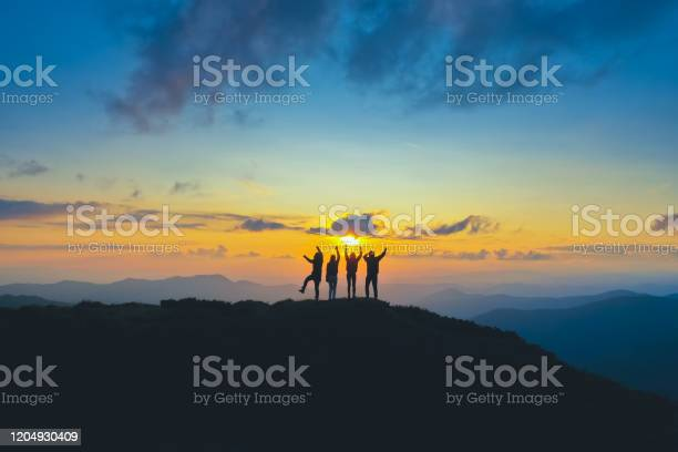 Photo of The four people standing on the beautiful mountain on the sunrise background