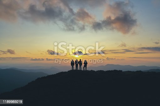 istock The four people standing on the beautiful mountain on the sunset background 1189985019