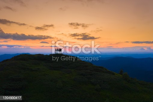 The four people standing on the picturesque mountain on the sunrise background