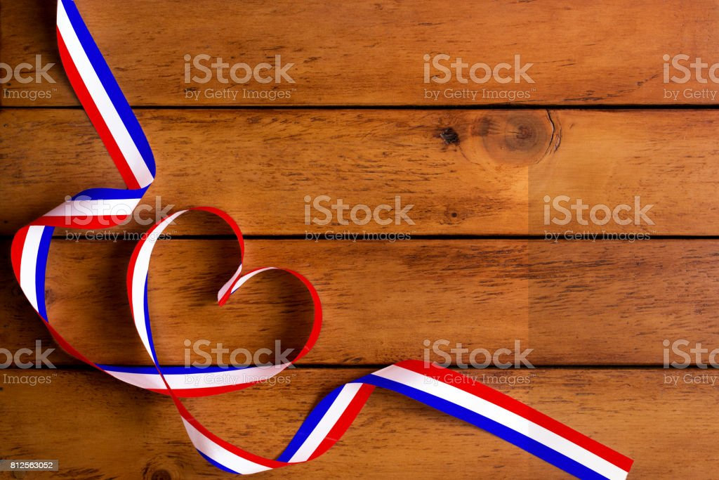 The France flag pattern and heart-shaped ribbon on wooden table/Bastille day stock photo