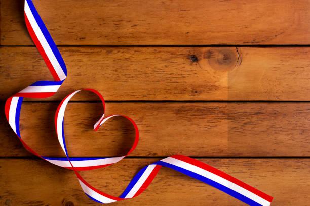 Le patron du pavillon France et ruban en forme de coeur sur la table en bois/fête - Photo