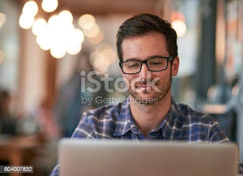 Shot of a young man using his laptop while sitting in a coffee shop