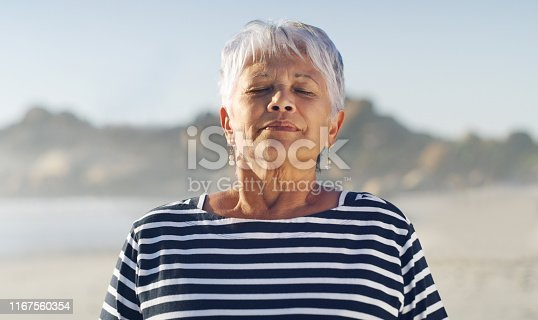 Cropped shot of an attractive senior woman taking a deep breath while standing alone on the beach