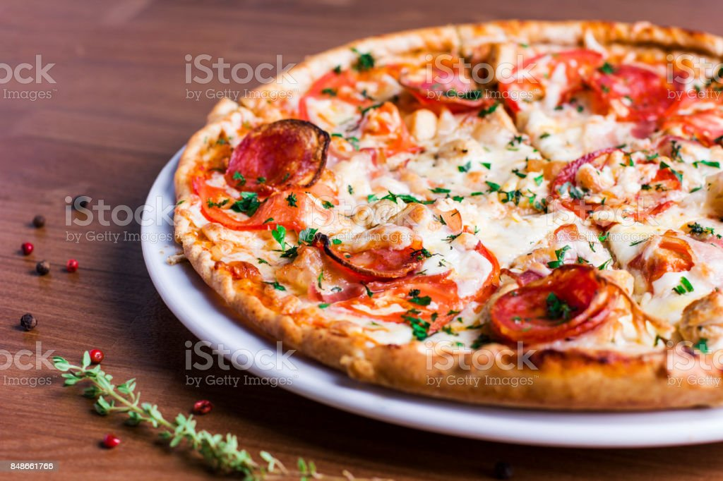 The fresh baked pizza with salami on white dish stock photo