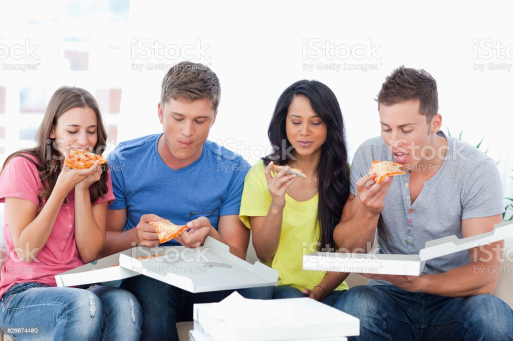 The friends tuck into the pizza just bought stock photo